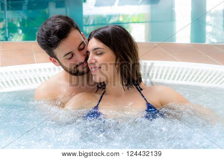 Close up portrait of romantic young couple enjoying jacuzzi in hotel spa.