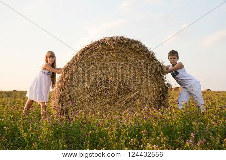 The boy and the girl on a glade with a haystack