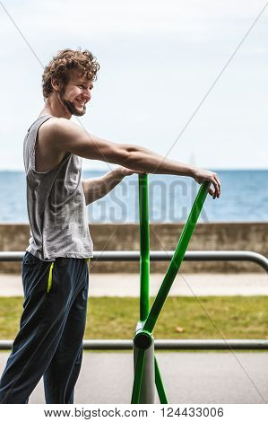 Active young man exercising on elliptical trainer machine. Muscular sporty guy in training suit working out at outdoor gym. Sport fitness and healthy lifestyle concept.