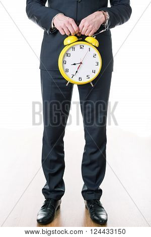 Close-up of young businessman in suit ready to work holding alarm clock. Man's hand in handcuff chained to watch