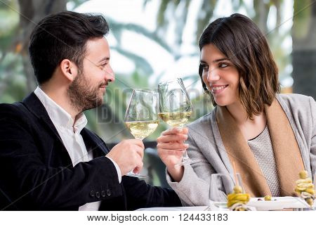 Close up of young handsome Couple sharing special moment white wine in restaurant.