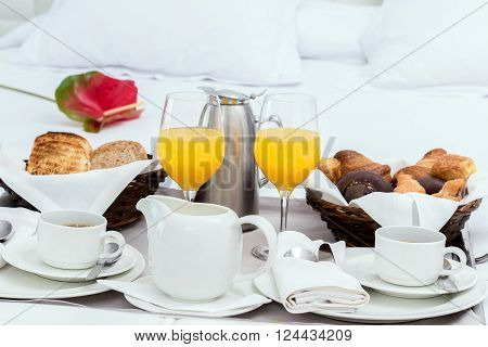 Close up of continental breakfast tray on bed with tea coffee toast and croissants.