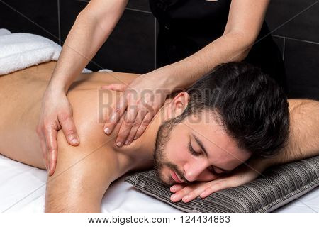 Close up of osteopath massaging young man's back.