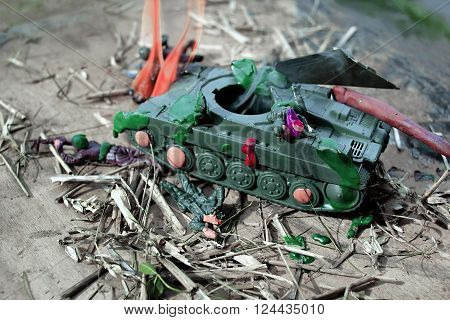 Closeup shot of destroyed toy tank and dead toy soldiers concept of war