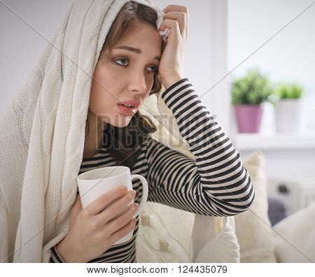 Sick woman covered with blanket holding cup of tea sitting on sofa couch.