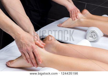 Close up of physiotherapists doing reflexology massage on couple.