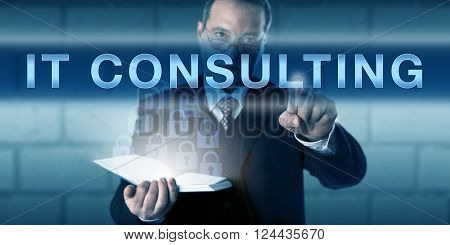 Male project manager is pressing IT CONSULTING on a visual touch screen interface. Business metaphor and information technology concept for advisory services providing technical expertise and skills.