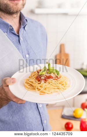 Spaghetti bolognese plate in man's or chef's hand - close up. Kitchen interior as background. Traditional italian food.