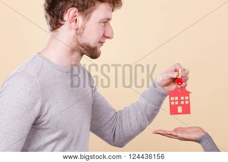 Male hand real estate agent or husband giving woman wife new house key, keys to property owner. Housing loan concept.