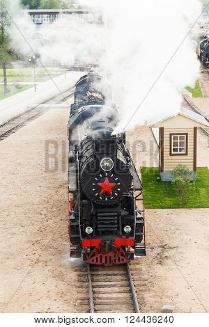 old black steam locomotive in Russia at the summer at the old railway station