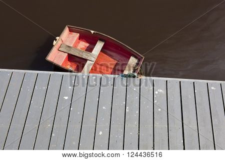 A small red boat tied up at a wooden jetty at the seaside