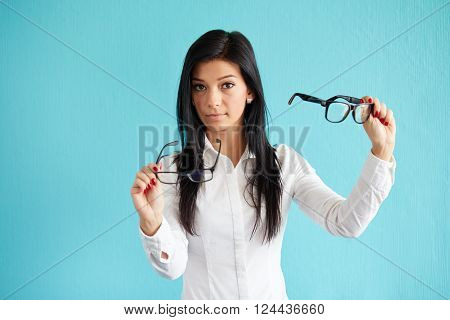Young Woman With Glasses Standing Before Blue Background