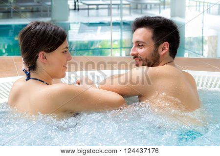 Close up portrait of attractive couple relaxing together in spa jacuzzi.