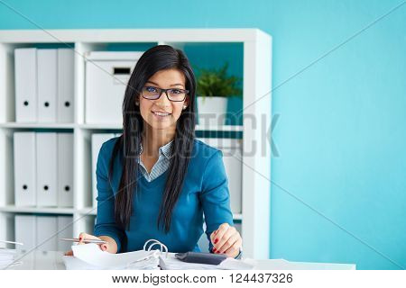 Young woman with glasses calculates tax in office