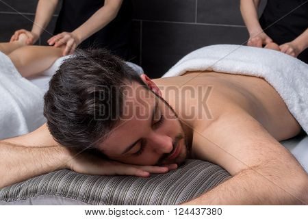 Close up portrait of young man at massage session in spa.