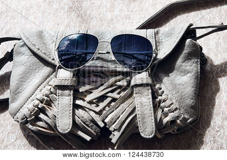Small gray women's handbag and sunglasses on grey background