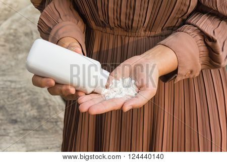 Close up women hand apply talcum powder