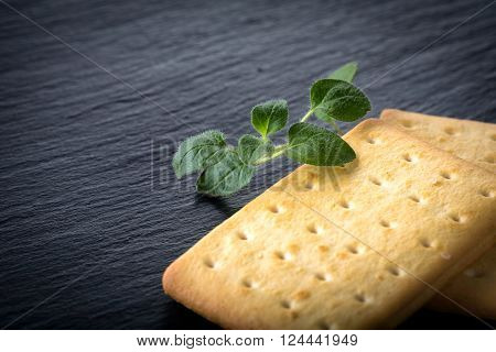 Dry Salted Crackers On Granite Plate With Oregano