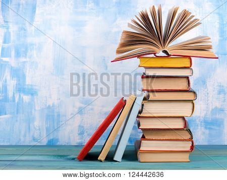 Composition with old vintage colorful hardback books, diary on wooden deck table and artistic blue background. Books stacking. Back to school. Copy Space. Education background