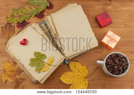 Dry leaves, old book and coffee on wooden background. Autumn romance. The book of romantic tales.