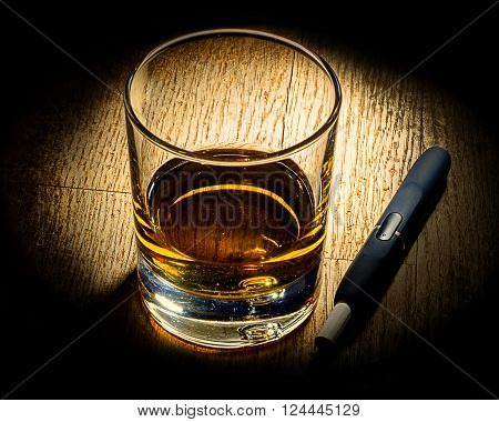 e-cigarette and glass of luxary alkohole on wooden table