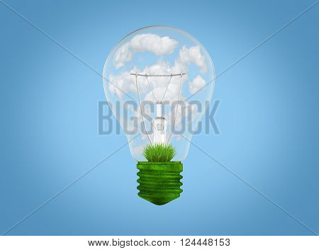 Natural energy concept. Light bulb with grass and clouds inside it.