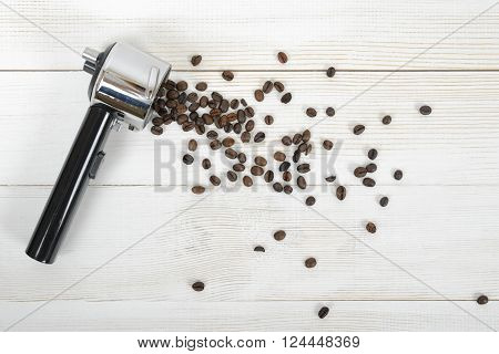Portafilter handle with scattered coffee beans on wooden surface in top view. Composition.