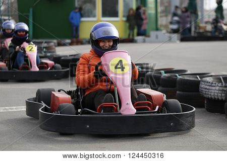 girl is driving Go-kart car with speed in a playground racing track. Go kart is a popular leisure motor sports.
