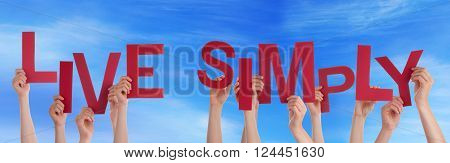 Many Caucasian People And Hands Holding Red Letters Or Characters Building The English Word Live Simply On Blue Sky