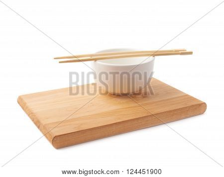Chinese dinner composition of the white ceramic bowl and wooden chopsticks over the small wooden board isolated over the white background