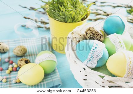 colorful easter eggs in a white wicker basket on blue table against the backdrop of greenery in decorative yellow bucket