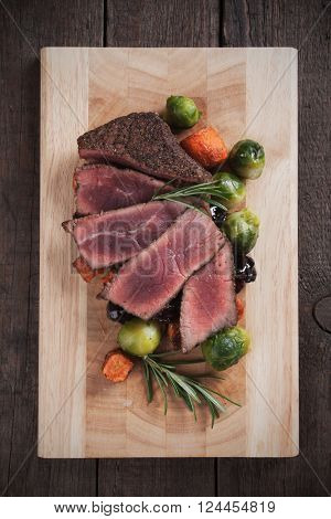 Medium rare beef steak with carrot and brussel sprout on wooden table