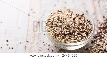 Pile of mixed raw quinoa, South American grain, in glass bowls on white rustic wooden background. Healthy and gluten free food. Copy space.