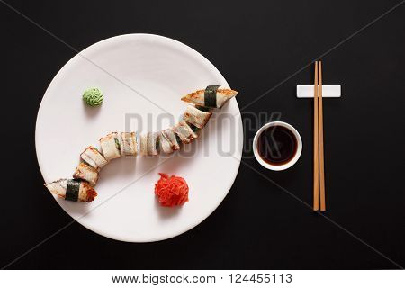 Japanese food restaurant, unagi sushi and roll plate set. One portion. Sushi with japanese fish eel, chopsticks, ginger and wasabi. Sushi at white round plate, black background. Top view, soy sauce.