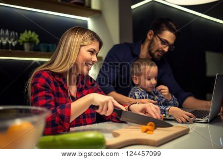 Mother preparing food while dad and son using laptop. Selective focus.