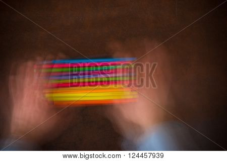 Wooden desktop with colorful pencil shaken by human hands