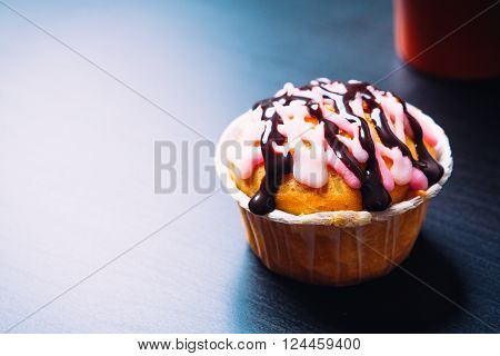 cupcake with pink frosting and red cup on a wooden background
