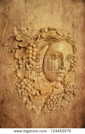 Textured Background with bust head of a Greek maiden with grapes leaves in statue form