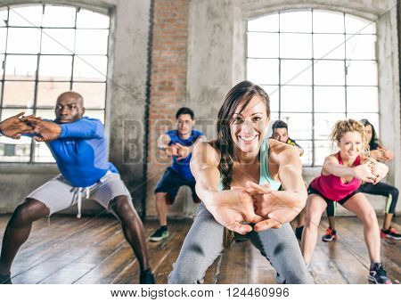 Multi-ethnic group of people training in a gym - Trainer and sportive persons doing squats in a fitness class