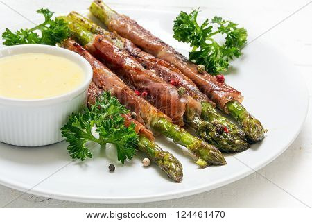 grilled green asparagus wrapped in prosciutto bacon and hollandaise sauce, white plate on a white wooden table, selected focus, narrow depth of field