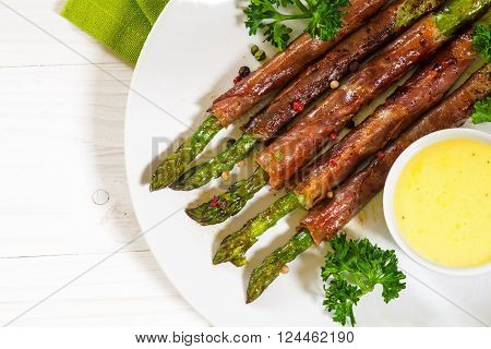 grilled green asparagus wrapped in prosciutto bacon, parsley garnish and hollandaise sauce, white plate on a white wooden background, view from above