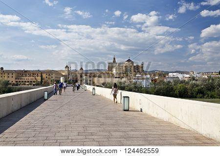 CORDOBA, SPAIN - September 10, 2015:  Using the ancient Via Augusta on the Roman Bridge across the Guadalquivir river on September 10, 2015 in Cordoba, Spain