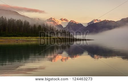 Gieke Inlet reflects fog and sunrise on placid waters within Glacier National Park, Alaska.
