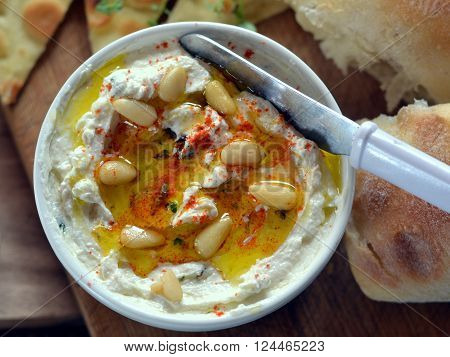 Labneh; Traditional Lebanese cheese dip made from yogurt, Shown in bowl, drizzled with olive oil and garnished with paprika and pine nuts. Viewed from above.