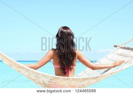 Rear view of a woman in bikini sitting on a hammock on a beach by the sea
