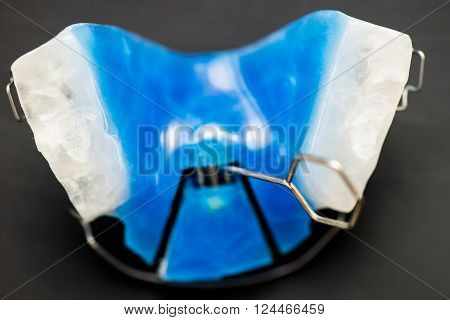 Dental Blue Removable Braces or Retainers for Teeth Orthodontic on Dark Grey Background ** Note: Shallow depth of field