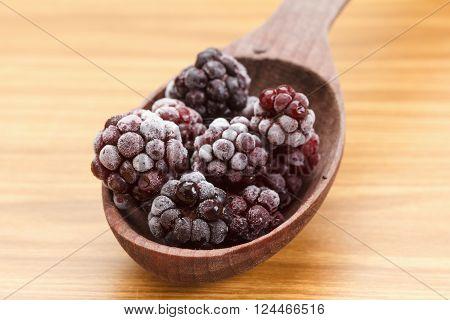 Macro view on frozen Blackberry fruits in spoon, wooden background