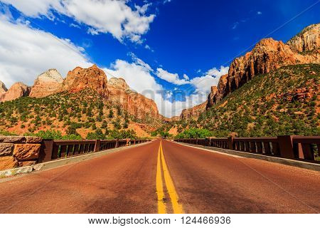 Zion National Park, USA. Excellent with red asphalt scenic road among the picturesque mountains of orange and red sandstone.