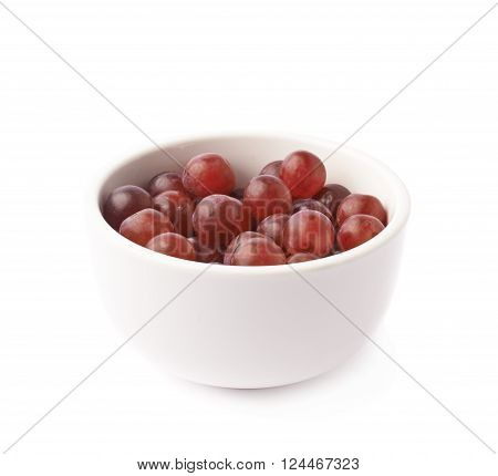 Bowl filled with the dark red grapes isolated over the white background