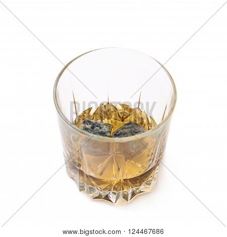 Glass tumbler filled with bourbon whiskey and granite cooling stones isolated over the white background